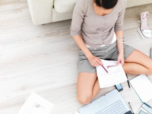 Wwoman holding paper sitting by laptop,running business